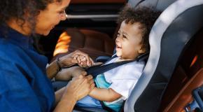 أم تضع طفلها في مقعد السيارة